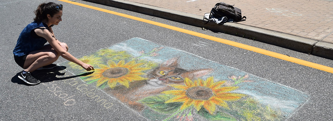 People creating chalk art in the street.